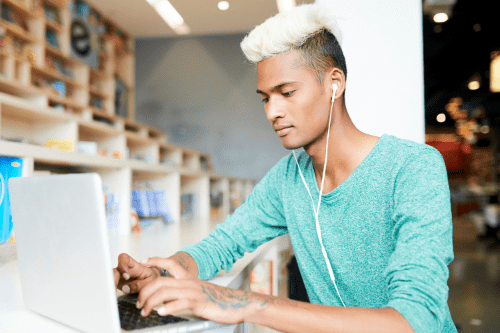 Student with bleached mohawk typing on laptop