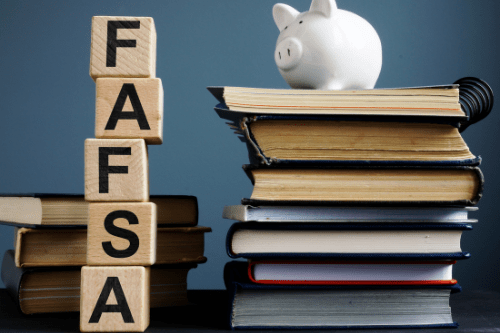 Stacked wooden blocks that read FAFSA and a piggy bank on top of books